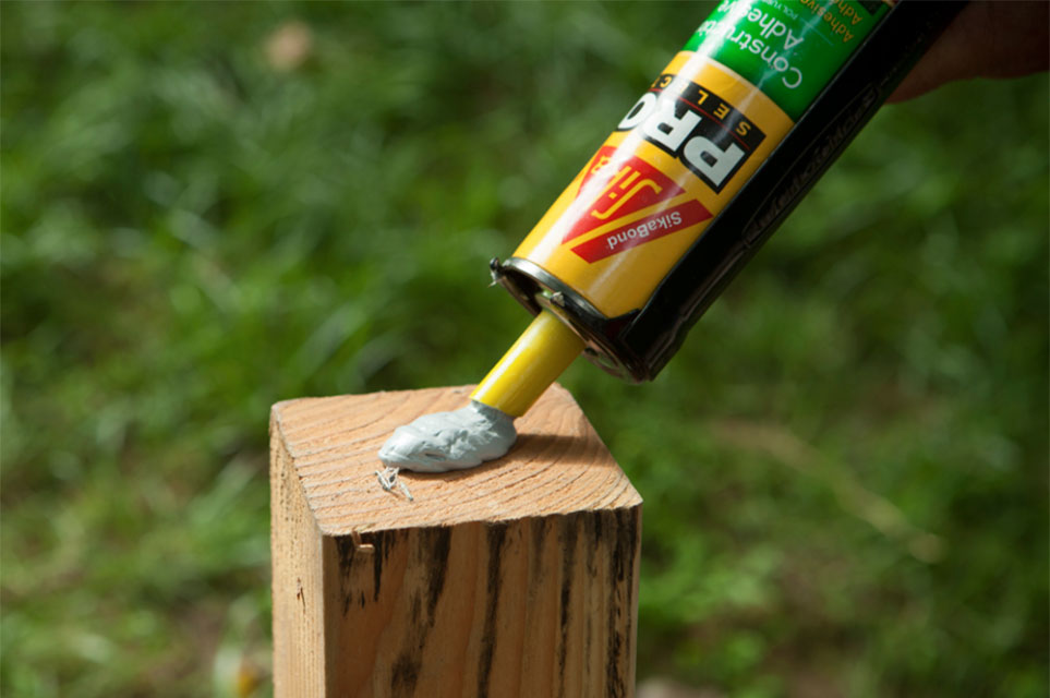 Applying SikaBond® Construction Adhesive to post.